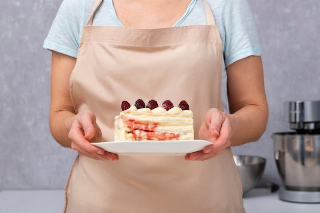 Morceau de gâteau de tranche de vanille avec des baies dans les mains du cuisinier.