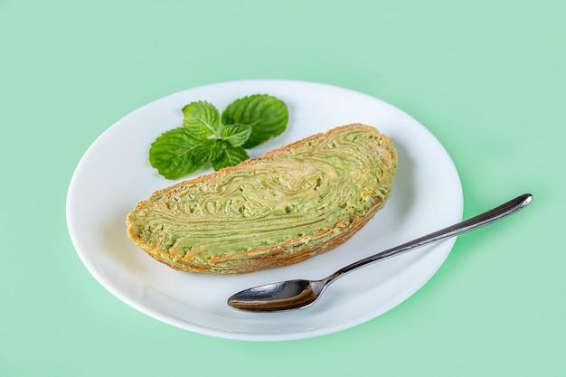 Morceau de gâteau vert aux pistaches. dessert coréen de thé matcha. nourriture crue