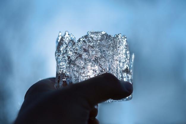 Un morceau de glace à la main