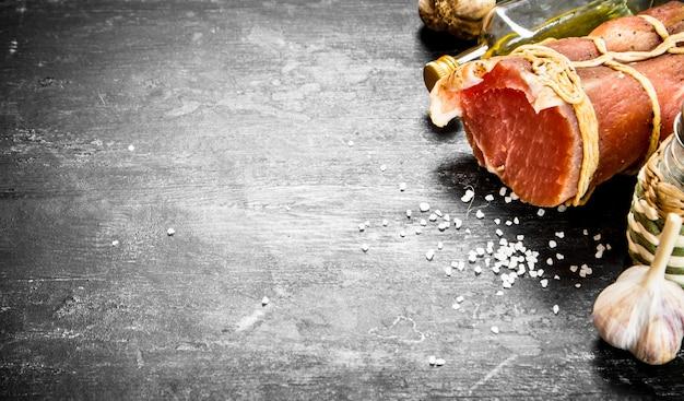 Morceau de jambon avec de l'ail, du sel et de l'huile d'olive.