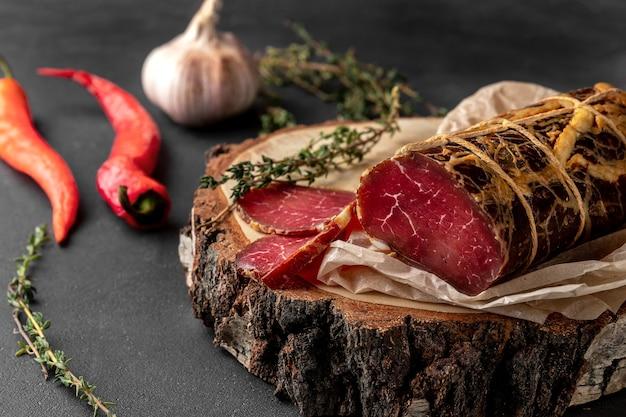 Morceau de jambon sec fumé rouge sur une coupe transversale en bois de l'arbre
