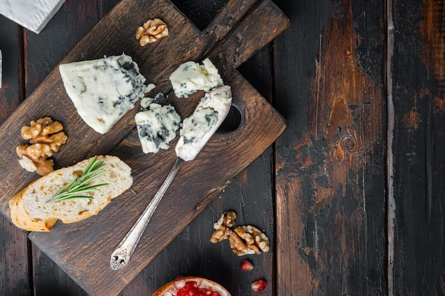Morceau de jeu de fromage gorgonzola, sur fond de bois foncé, vue de dessus avec copie espace pour le texte
