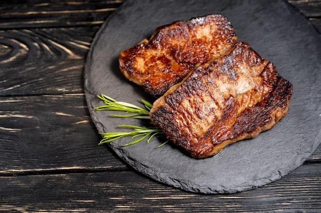 Morceau juteux de viande frite se trouve sur une plaque de pierre contre une table en bois noire