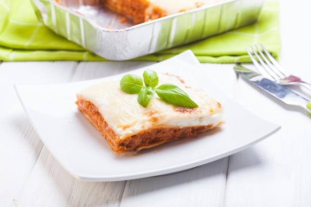 Morceau de lasagne bolognaise aux feuilles de basilic dans une assiette blanche