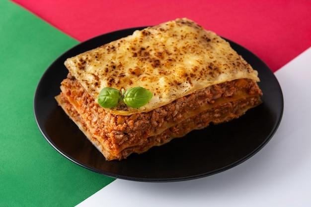Morceau de lasagne à la viande sur une plaque noire