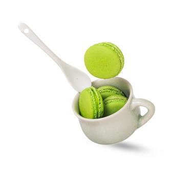 Un morceau de macaron vert tombant sur une tasse en céramique verte tendre remplie de plus de macarons
