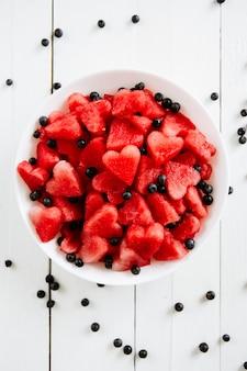 Morceau de melon d'eau et coeurs sur fond blanc