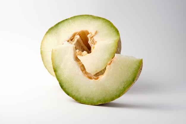 Morceau de melon mûr avec des graines sur fond blanc