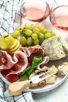 Morceau de noix de fromage bleu et de miel, prosciutto aux raisins vibrants, vin rose, couteau à fromage, fourchettes, noix et miel, concept de célébration de fête. vue de dessus.