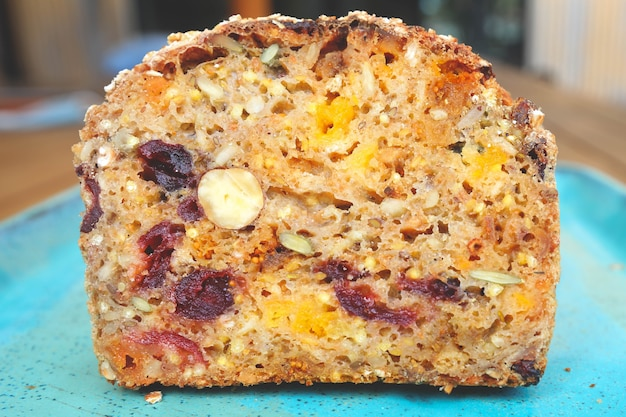 Un morceau de pain aux fruits secs sur plaque bleue, abricots secs, raisins secs, pruneaux et noisettes, vue de dessus.