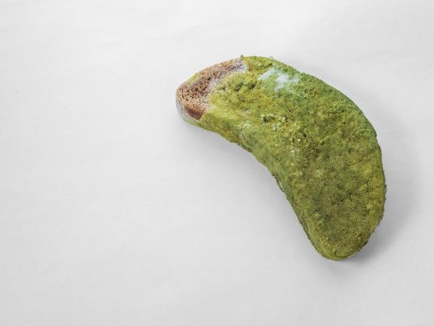 Un morceau de pain couvert de moisissure verte sur fond blanc isoler.