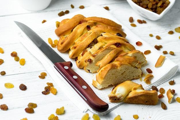 Morceau de pain tressé sucré avec des raisins secs et un couteau sur une serviette de cuisine sur un fond en bois blanc.