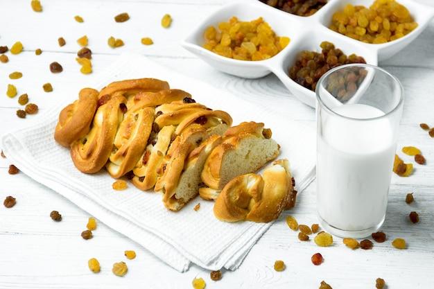 Morceau de pain tressé sucré avec des raisins secs et du lait sur un essuie-tout sur un fond en bois blanc.