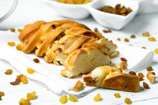 Morceau de pain tressé sucré avec des raisins secs sur un torchon