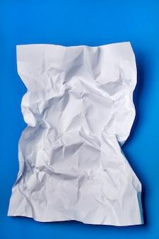 Un morceau de papier blanc froissé sur un fond bleu.