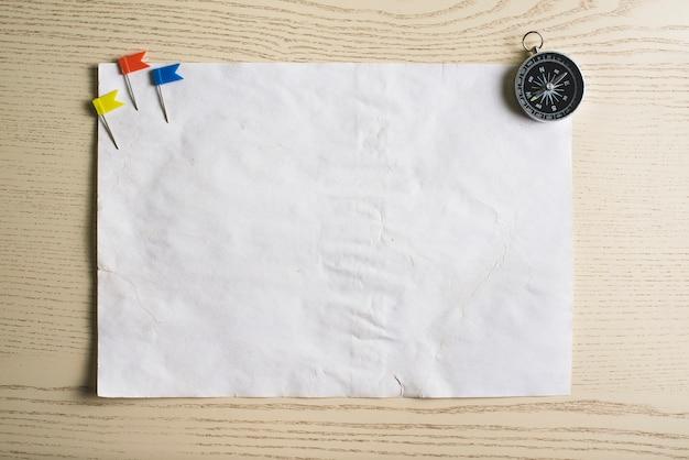Morceau de papier avec boussole et quelques pointeurs de couleur