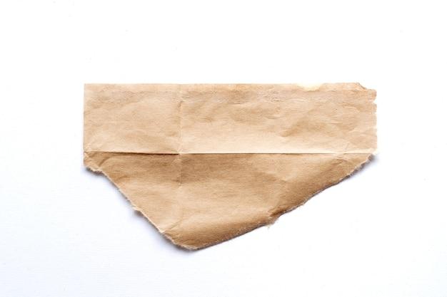 Morceau de papier brun déchiré sur fond blanc