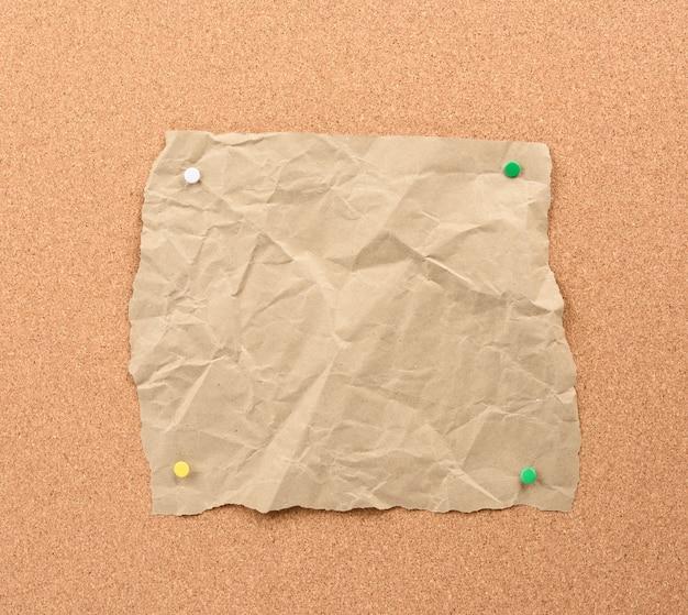 Morceau de papier déchiré brun épinglé avec des boutons de fer sur un panneau de liège brun