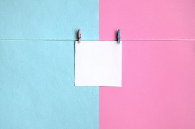 Un morceau de papier est suspendu à une corde avec des chevilles sur la texture