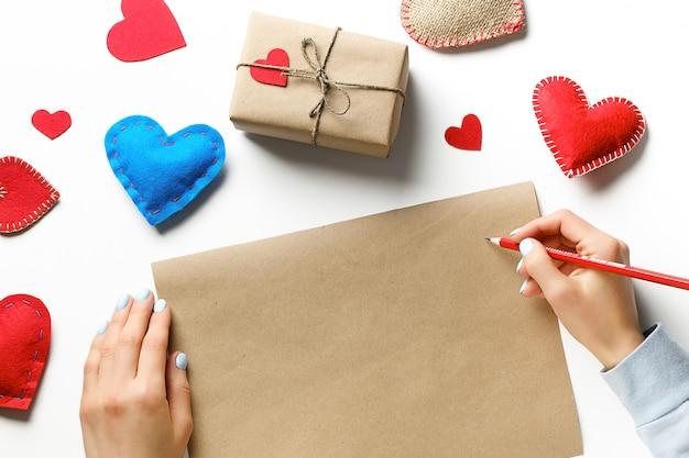 Morceau de papier kraft à côté de coeurs en feutre et boîte-cadeau