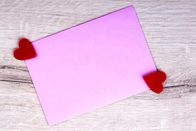 Morceau de papier rose et coeurs. carton sur fond de bois. créez une belle carte de vœux. présentez l'amour lors d'une journée spéciale.