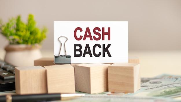 Morceau de papier avec le texte cash back sur des cubes en bois avec des billets, un stylo, une calculatrice noire et une plante verte