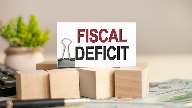 Morceau de papier avec le texte déficit fiskal. cubes en bois, billets, stylo, calculatrice noire et plan vert