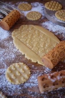 Un morceau de pâte avec une impression de voitures pour enfants. rouleaux en bois pour biscuits