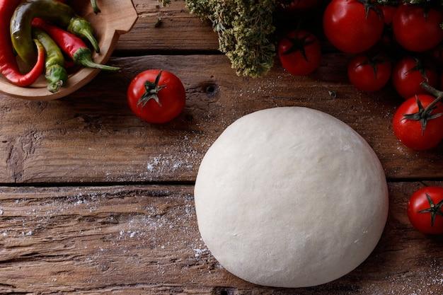 Morceau de pâte sur une table en bois entourée de tomates et de poivrons
