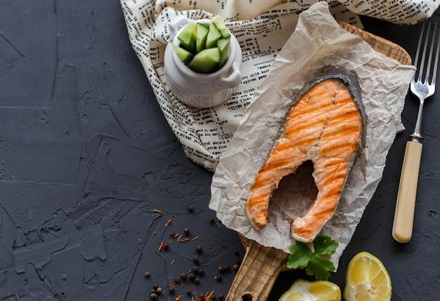 Morceau de poisson rouge grillé sur planche de bois et serviette textile, avec citron, herbes et concombres