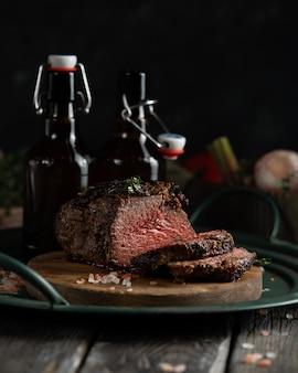 Un morceau de rôti de bœuf cuit au four et deux bouteilles de bière brune sur un plateau en fer vert de style campagnard