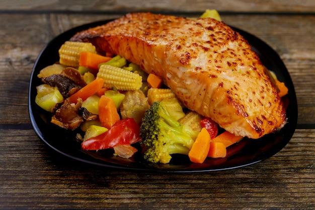 Un morceau de saumon cuit au four avec des légumes sautés asiatiques sur une plaque noire. fermer.