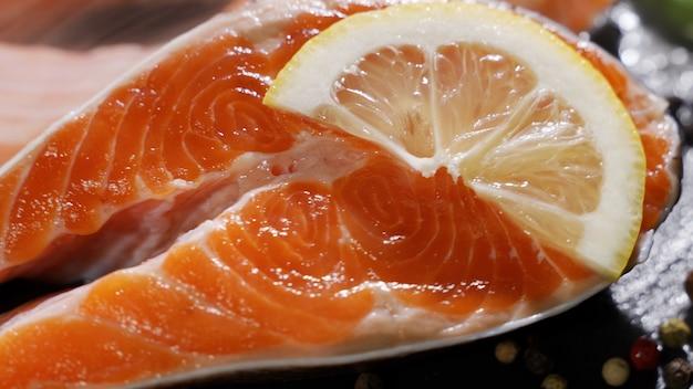 Morceau de saumon frais placé sur une planche à découper sur une table de cuisine avec des épices citron