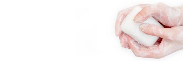 Morceau de savon blanc. savon antibactérien dans les mains. désinfection des mains avec du savon. propreté et hygiène au quotidien. hygiène des mains