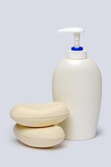 Morceau de savon et bouteille de savon liquide sur fond gris clair avec chemin de détourage