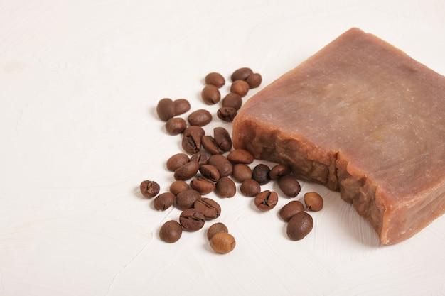 Morceau de savon maison cacao et grains de café, fond beige copie sapce