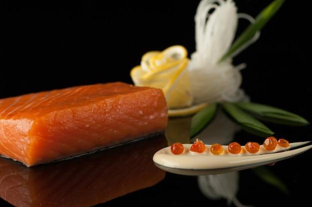 Morceau de sushi au citron et feuille sur fond sombre avec reflet