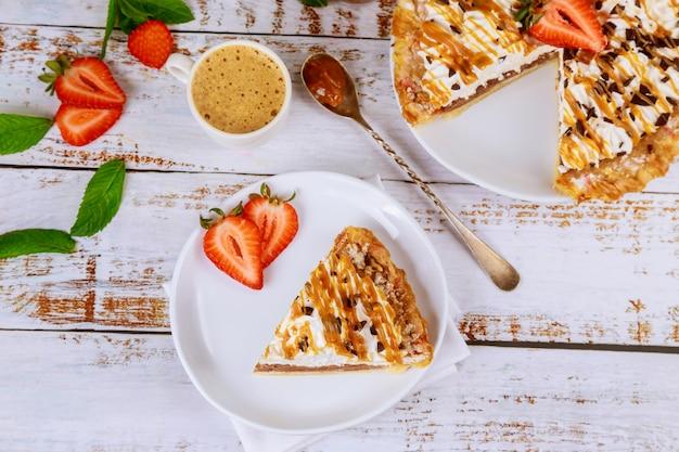 Morceau de tarte au caramel avec une tasse de café