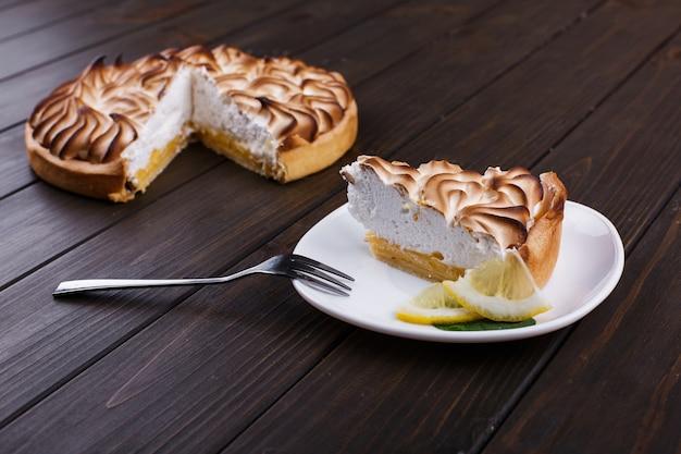 Morceau de tarte au citron avec crème blanche servi sur une plaque blanche