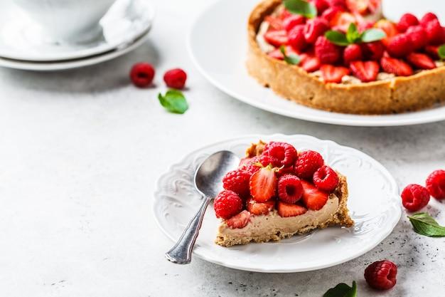 Morceau de tarte aux baies avec framboises, fraises et crème sur une plaque blanche