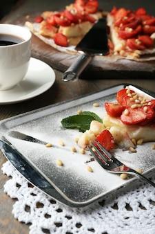 Morceau de tarte aux fraises sur plateau, sur fond de bois rustique