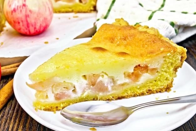 Morceau de tarte aux pommes avec sauce à la crème sure dans une assiette blanche, cannelle, fruits et serviette sur fond de planche de bois foncé