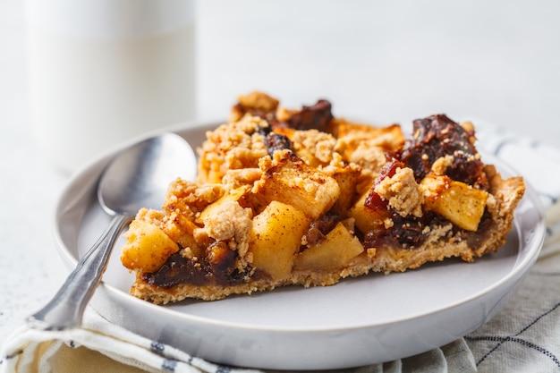 Morceau de tarte aux pommes végétalien à la cannelle, fond blanc. concept alimentaire végétalien.