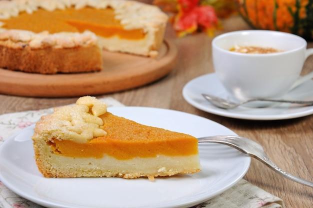 Un morceau de tarte à la citrouille parfumée sur une table avec une tasse de café à la citrouille avec de la crème et de la cannelle