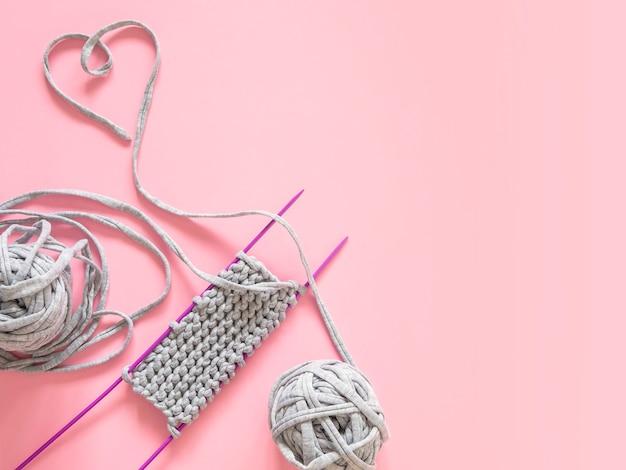 Un morceau de tricot avec une pelote de laine grise et des aiguilles à tricoter violettes sur fond rose.