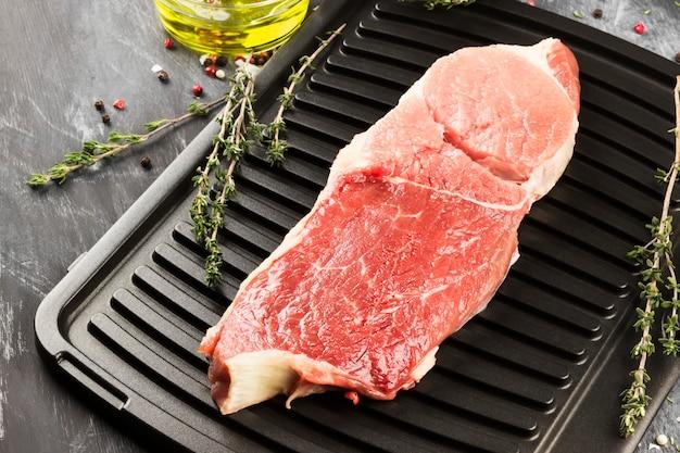 Morceau de viande de bœuf crue sur un grill avec du poivre, de l'huile d'olive et un thym sur fond sombre