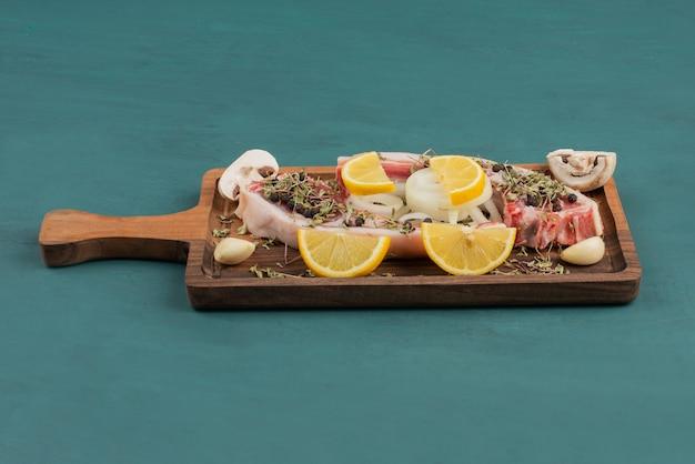 Morceau de viande crue avec des légumes sur planche de bois.