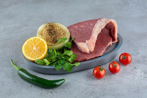 Morceau de viande crue placé sur une table en pierre.