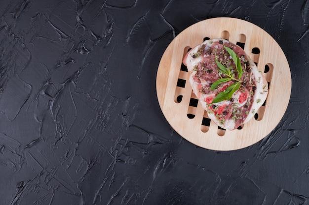 Morceau de viande crue sur plaque en bois décorée de menthe fraîche sur fond sombre.