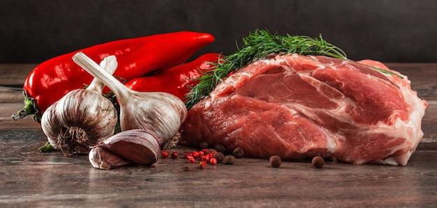 Morceau de viande crue prêt pour la préparation avec des légumes verts et des épices